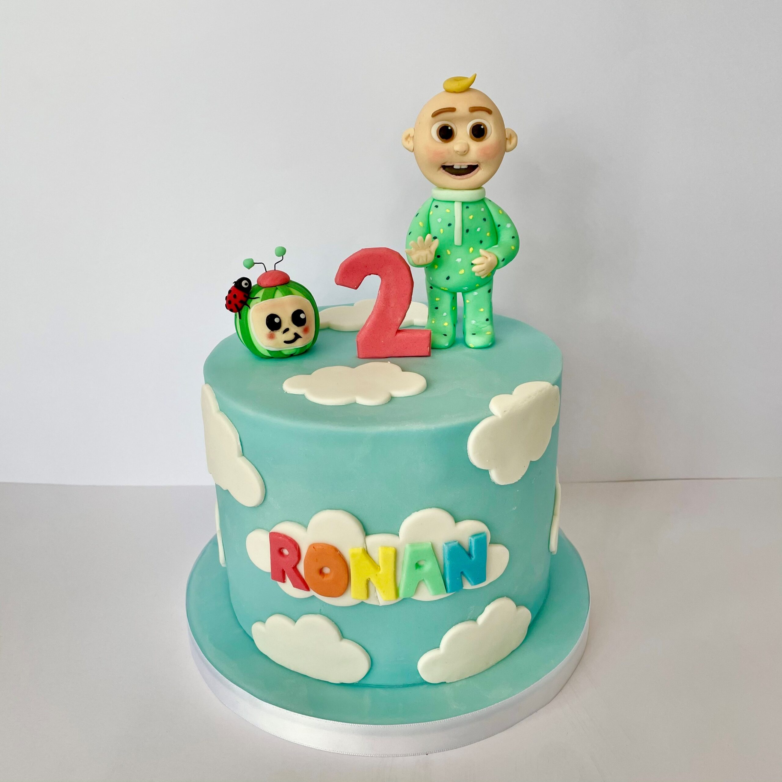 Cocomelon figure with ladybird, JJ standing up next to a red number two. On top of a blue cake with clouds and the name Ronan on the front side of the cake